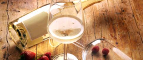 Eine Flasche Prosecco und ein Obstkorb